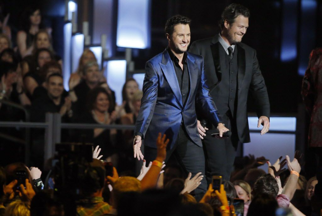 Hosts Luke Bryan (center) and Blake Shelton walk across the stage during the 2015 Academy of County Music Awards Sunday, April 19, 2015 at AT&T Stadium in Arlington, Texas.