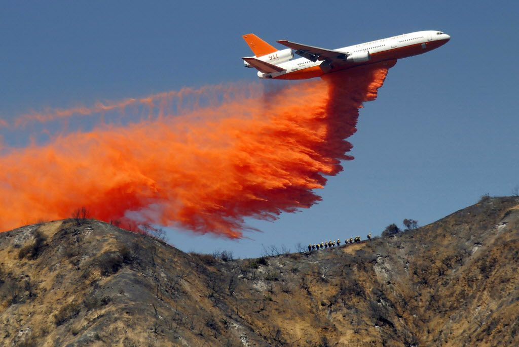 In this Tuesday, Sept. 24, 2013 file photo, a DC-10 airplane tanker drops fire retardant to battle a wildfire in the San Gabriel Mountains in Azusa, Calif. AP Photographer Nick Ut will be retiring from the AP in March 2017 after 51 years of taking photographs from the front lines of the Vietnam War to the red carpets of Hollywood.