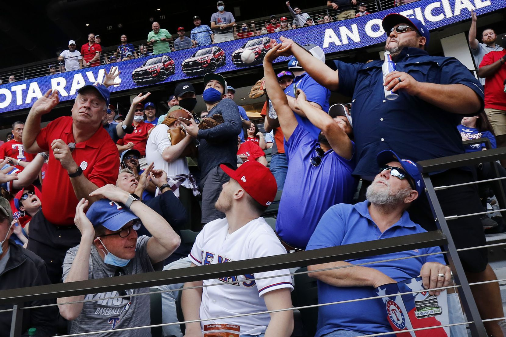 Texas Rangers fans Adam Ramirez (right) and Tommy Munoz (second from right) try to catch a foul ball on Opening Day at Globe Life Field in Arlington, Monday, April 5, 2021. Luckily for Grady Chandler of Dallas (left), the ball bounced away and he picked it up. The Rangers were facing the Toronto Blue Jays in the home opener. (Tom Fox/The Dallas Morning News)
