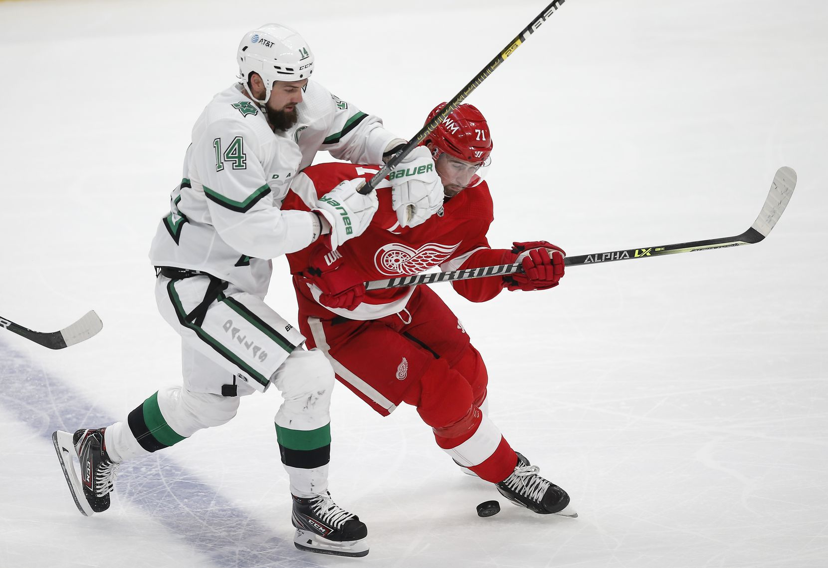 Dallas Stars forward Jamie Benn (14) battles Detroit Red Wings forward Dylan Larkin (71) for the puck during the first period of an NHL hockey game in Dallas, Monday, April 19, 2021. (Brandon Wade/Special Contributor)