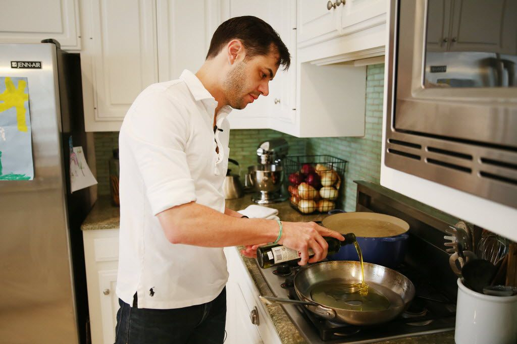 Chef Julian Barsotti adds oil to a pan while cooking a pasta dish at his home in Dallas.