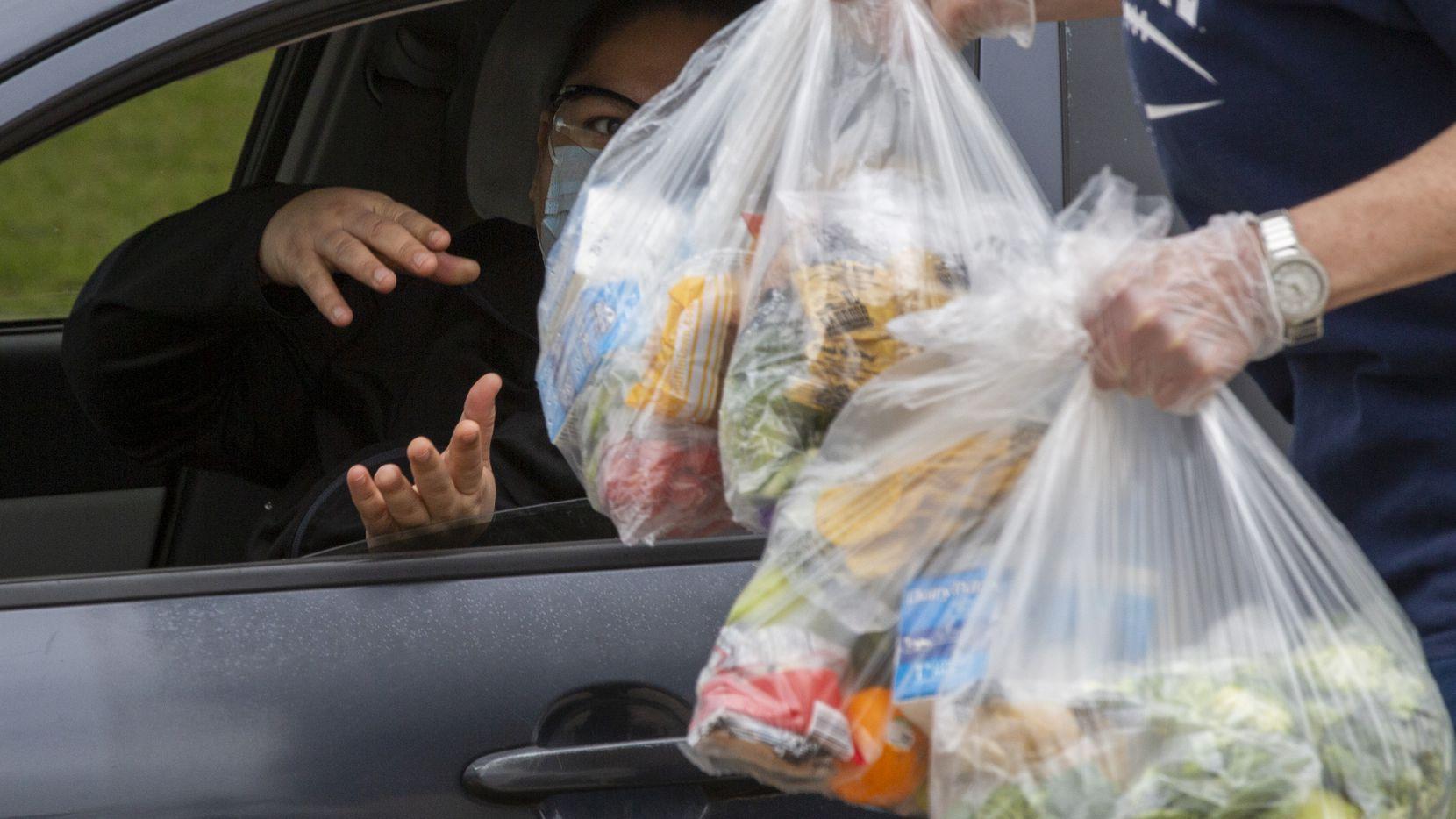Voluntarios del DISD entregan paquetes de alimentos a familias este jueves.