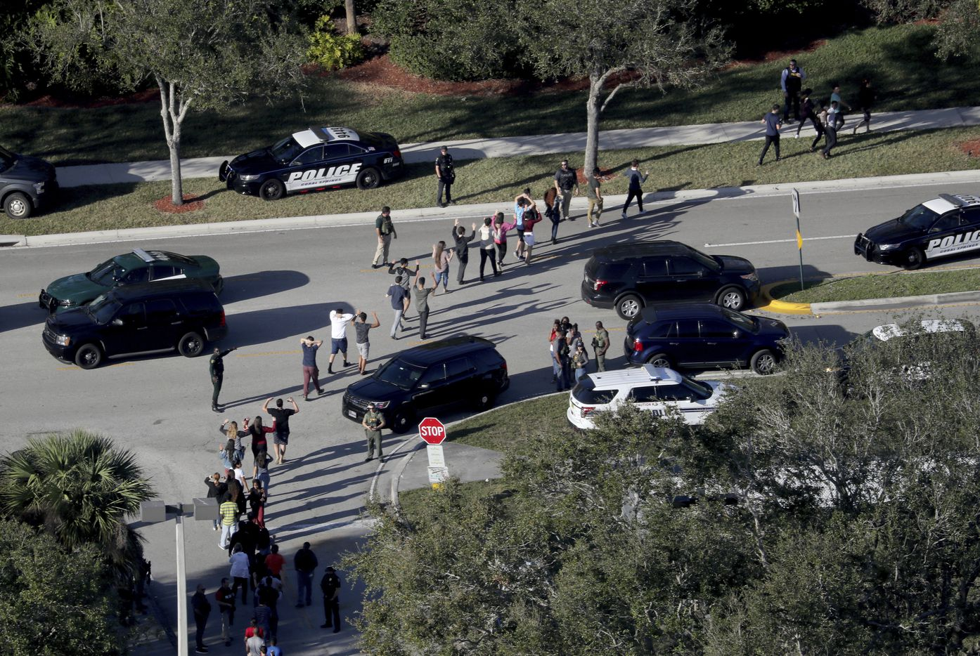 Students hold their hands in the air as they are evacuated by police from Marjory Stoneman Douglas High School in Parkland, Fla., on Wednesday, Feb. 14, 2018, after a shooter opened fire on the campus.