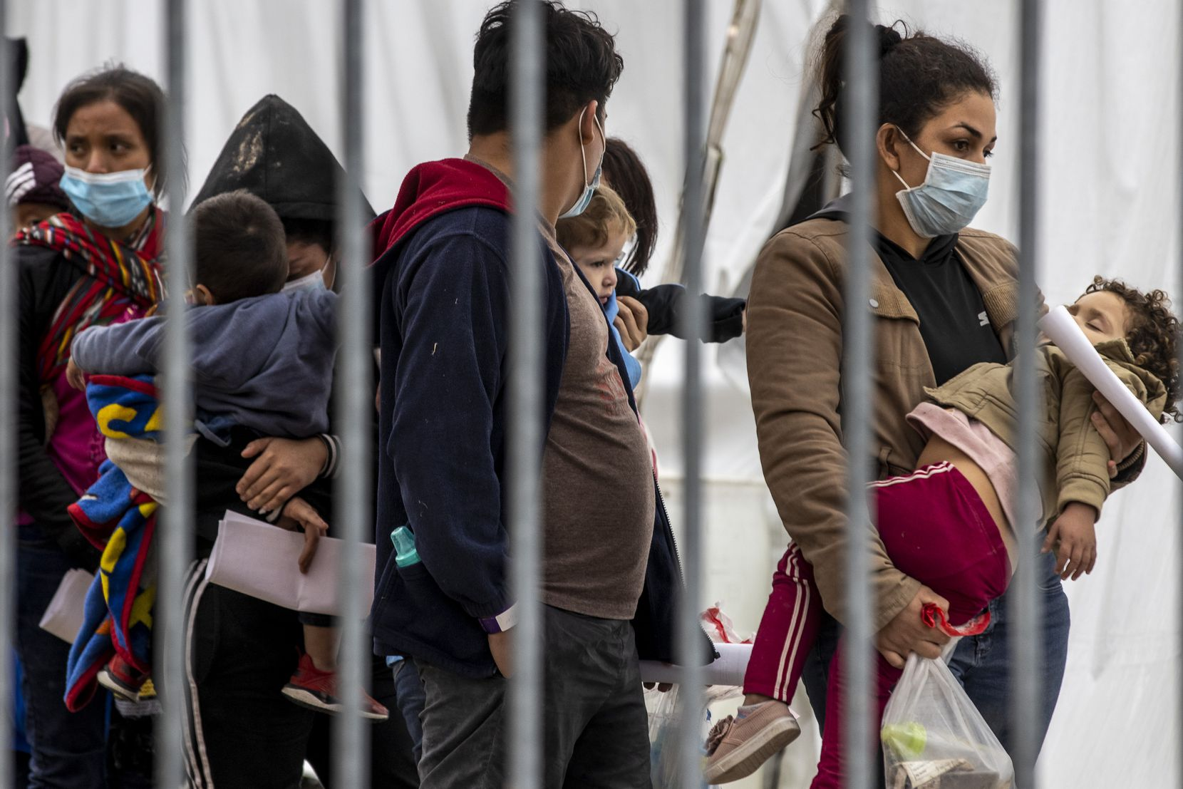 A woman carrying a small child waits in line with other migrant families to be tested for COVID-19 at a tent facility set up across the bus station in McAllen, Texas, on Sunday, March 28, 2021. These families were then transported to the nearby respite center operated by Catholic Charities.