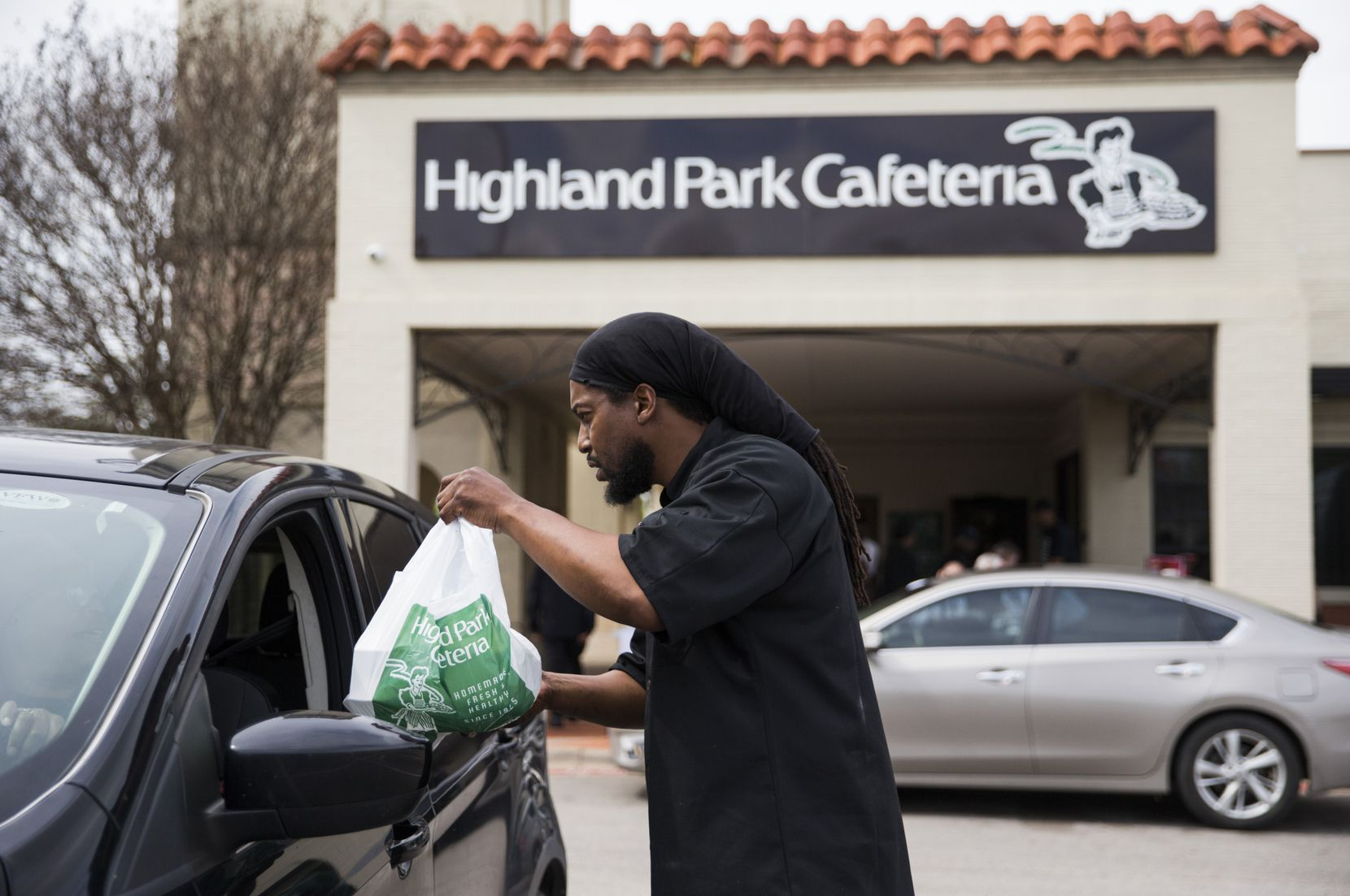 Executive chef Johnny Howard delivered a meal to a driver outside Highland Park Cafeteria last week. Employees handed out free meals outside the cafeteria after Dallas eatery and bar dining areas were closed to help slow the spread of COVID-19