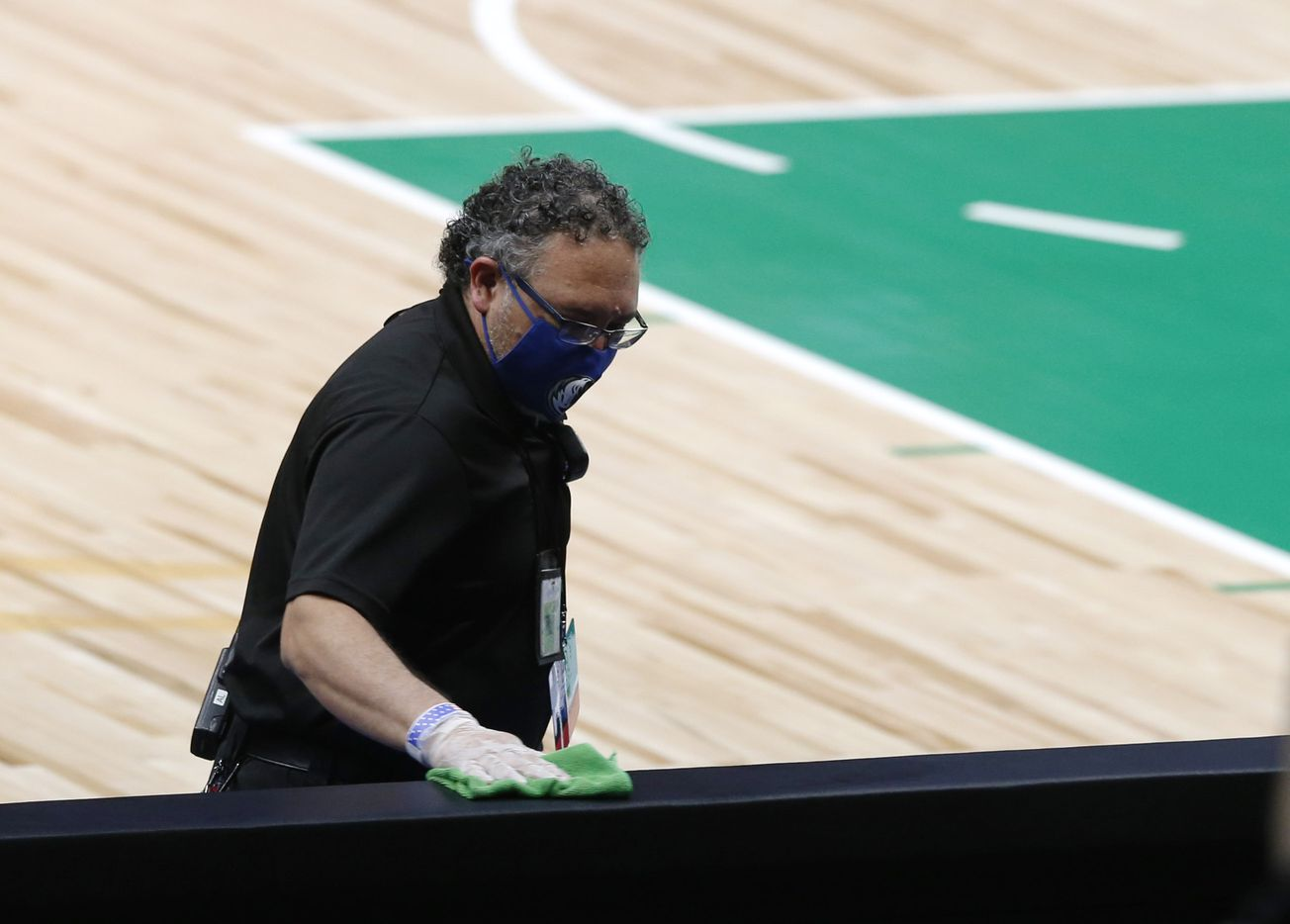 Employees clean the an area next to the court before a game between the Dallas Mavericks and Charlotte Hornets for the home opener at American Airlines Center on Wednesday, December 30, 2020 in Dallas. (Vernon Bryant/The Dallas Morning News)
