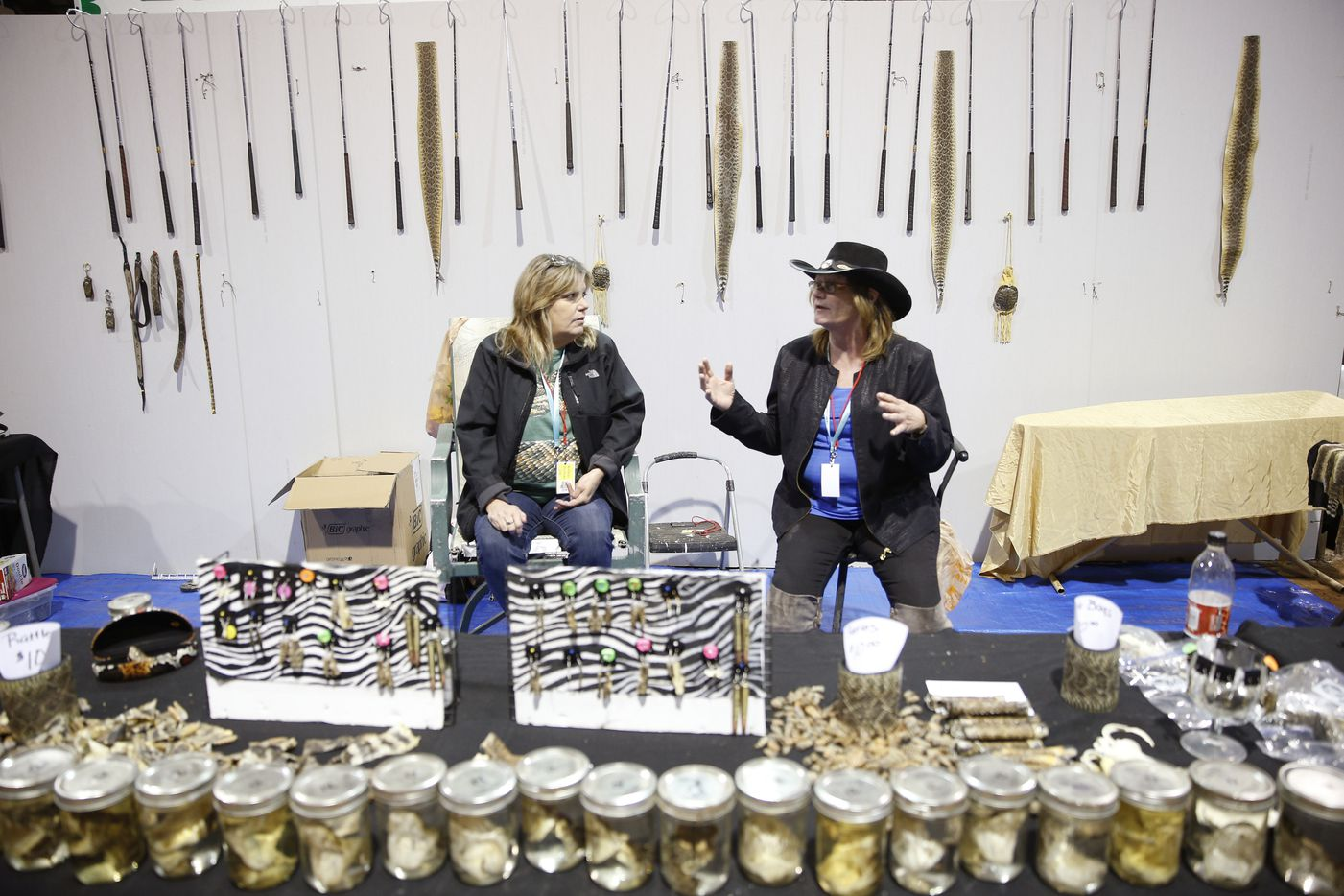 Lisa Cochran (left) and Janna Lasly talk while selling rattlesnake items  at their shop, Reptiles Unlimited, during the Sweetwater Rattlesnake Roundup. (Nathan Hunsinger/The Dallas Morning News)