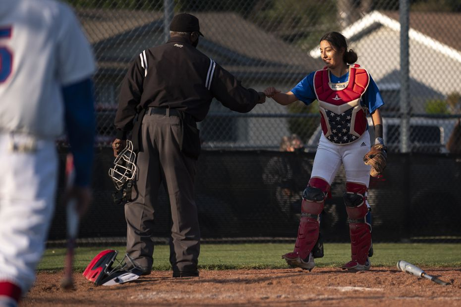 Adamson High School senior Tatyana Beltran (2), receives a fist bump from an umpire after a job well done on a play during a baseball game versus Spruce High School, on Tuesday, April 20, 2021 at Spruce High School in Dallas. Beltran, 18, has been playing baseball since the age of 9; some of her current teammates grew-up with her playing baseball. Beltran pitches, plays in-field at third base, catches, and isn't afraid to get hit by a pitch for she was hit twice on Tuesday without attempting to dodge the ball.