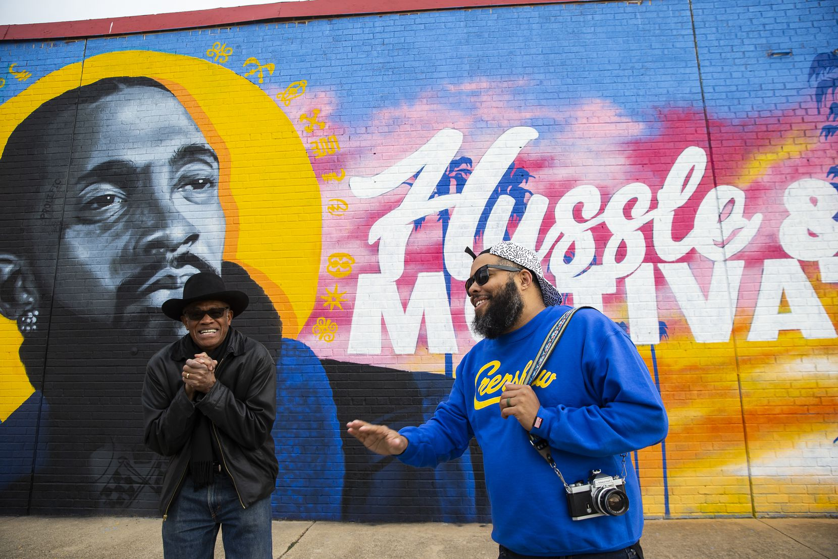 Glendale Shopping Center owner Al Herron (left) shares a laugh while talking to artist Jeremy Biggers in front of his mural dedicated to the late rapper, entrepreneur and community activist Nipsey Hussle at the Glendale Shopping Center on Feb. 22, 2020 in Dallas.