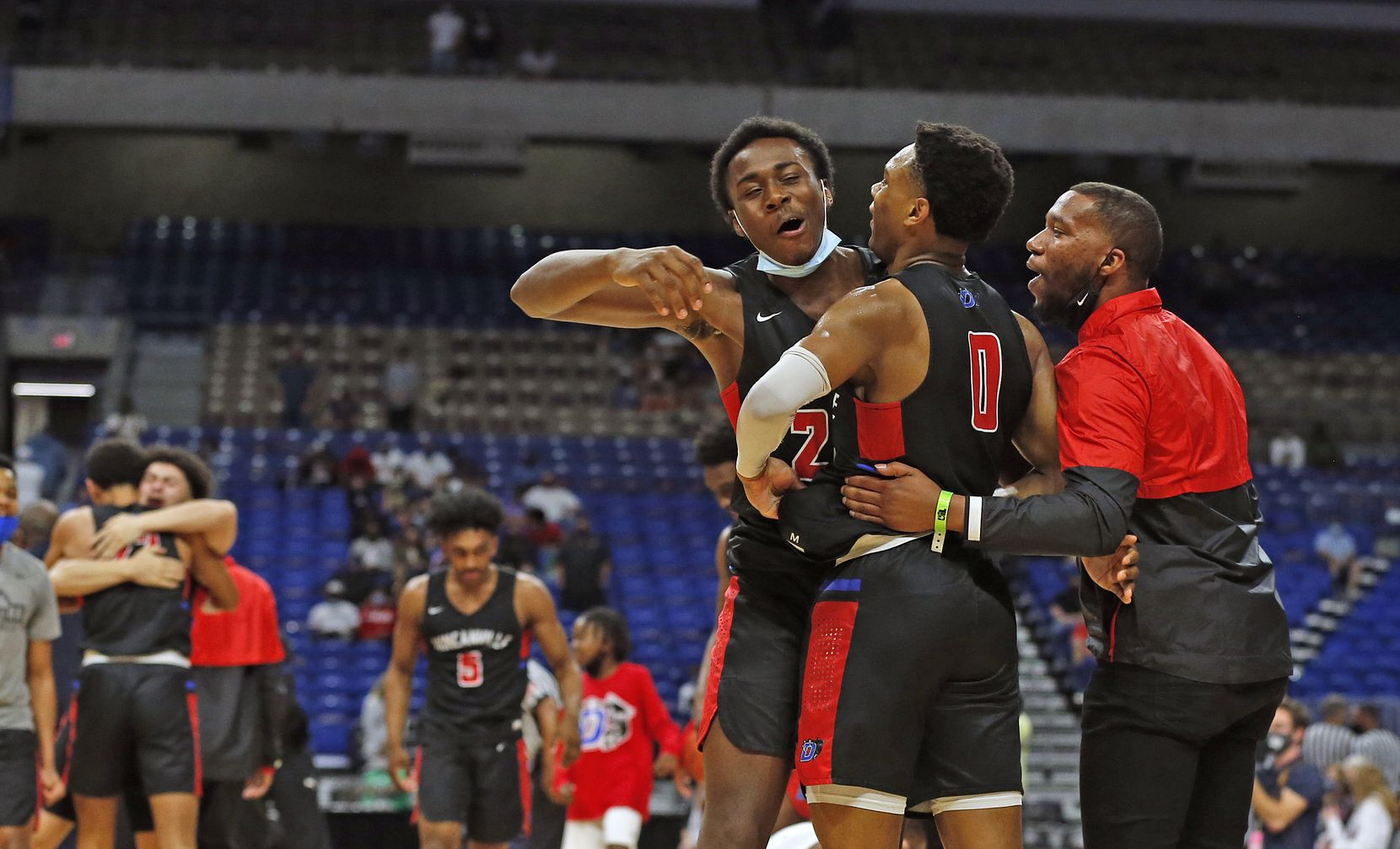 Duncanville Zhuric Phelps #0 is hugged by DeCannon Wickware and staff at the end of the game. UIL boys Class 6A basketball state championship game between Duncanville and Austin Westlake on Saturday, March 13, 2021 at the Alamodome.