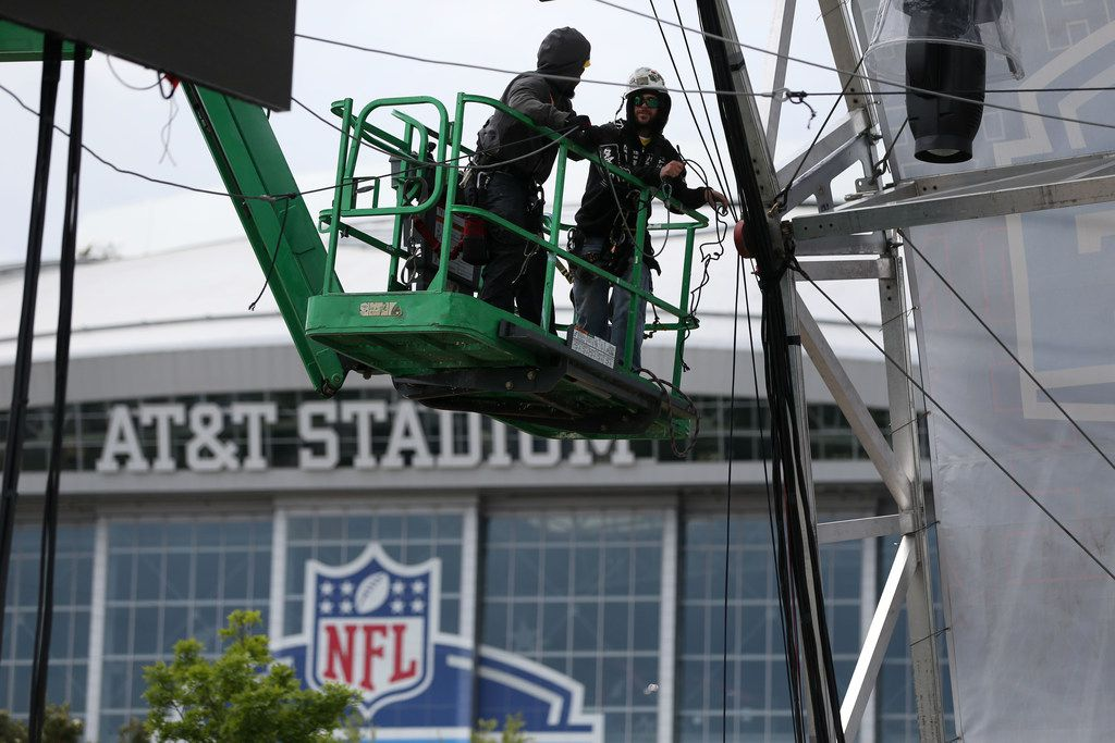 Workers secure a large video board above a walkway in preparation for the NFL Draft Experience outside AT&T Stadium in Arlington, Texas on Wednesday, April 25, 2018. (Rose Baca/The Dallas Morning News)