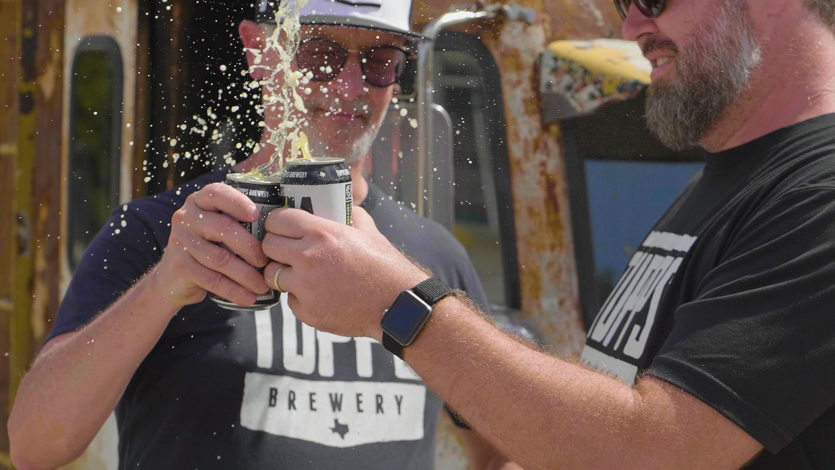 Keith Lewis, founder and president of TUPPS, and Chris Lewis, head brewer, make a toast.