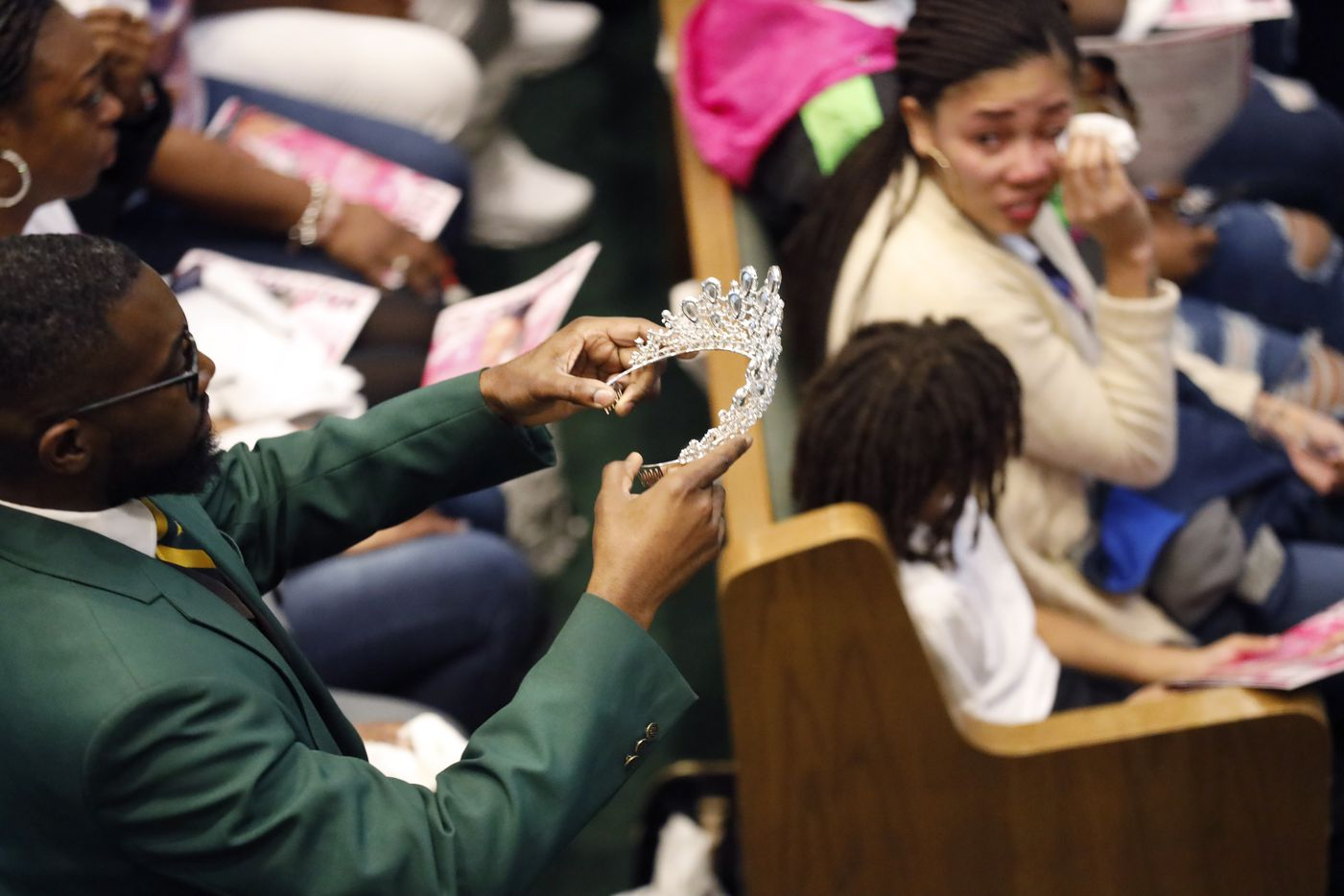 Funeral attendant Kevin Brooks of Evergreen Memorial Funeral Home marches down the aisle with a tiara for LaTiffiney Rodgers, 26, during a celebration of life and funeral service at the CrossRoads Covenant Church in DeSoto, Texas, Saturday, February 22, 2020.