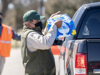 Inocencio Martinez loads a case of bottled water in a pickup truck, Monday, February 22, 2021 during a water distribution organized by the City of Dallas' Office of Emergency Management. More than a week after winter storms hit Texas, many area residents, including hundreds of apartment dwellers in Garland, remain without running water.