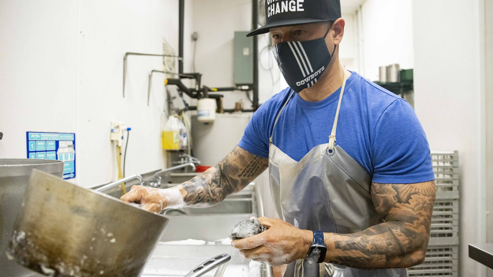 Dallas Police Chief Eddie García checks a pot before washing it during his shift as an undercover dishwasher at Café Momentum, which employs formerly incarcerated youth, on Friday, May 14, 2021, in Dallas. (Juan Figueroa/The Dallas Morning News)