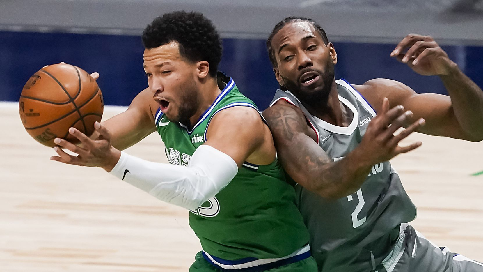 Dallas Mavericks guard Jalen Brunson (13) grabs a rebound away from LA Clippers forward Kawhi Leonard (2) during the first quarter of an NBA basketball game at American Airlines Center on Wednesday, March 17, 2021, in Dallas. (Smiley N. Pool/The Dallas Morning News)