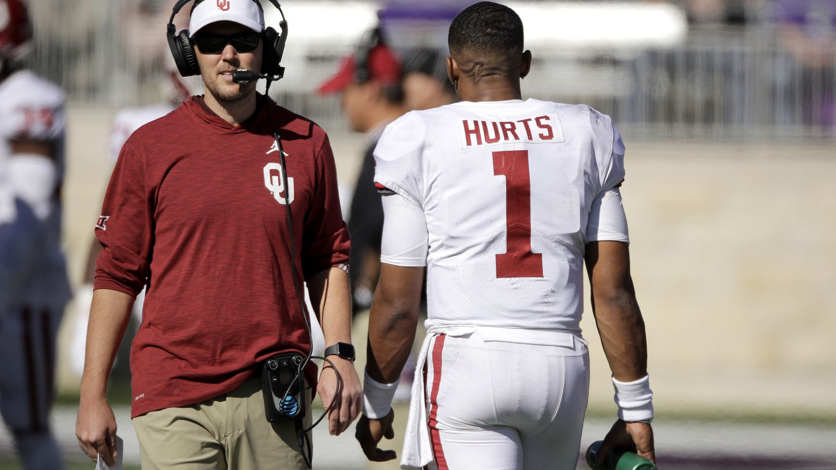 Oklahoma quarterback Jalen Hurts (1) and head coach Lincoln Riley pass each other on the sideline during the final moments of an NCAA college football game against Kansas State Saturday, Oct. 26, 2019, in Manhattan, Kan. Kansas State won 48-41. (AP Photo/Charlie Riedel)
