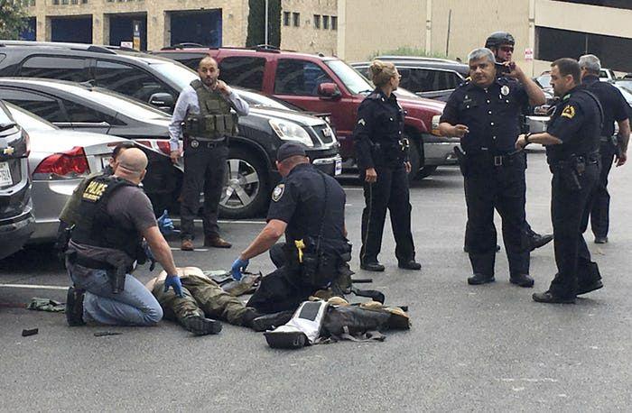 Los oficiales de policía atienden a un hombre al que derribaron después de que disparó al edificio federal y al juzgado de Earle Cabell en el centro de Dallas el lunes 17 de junio de 2019. (Tom Fox / DMN
