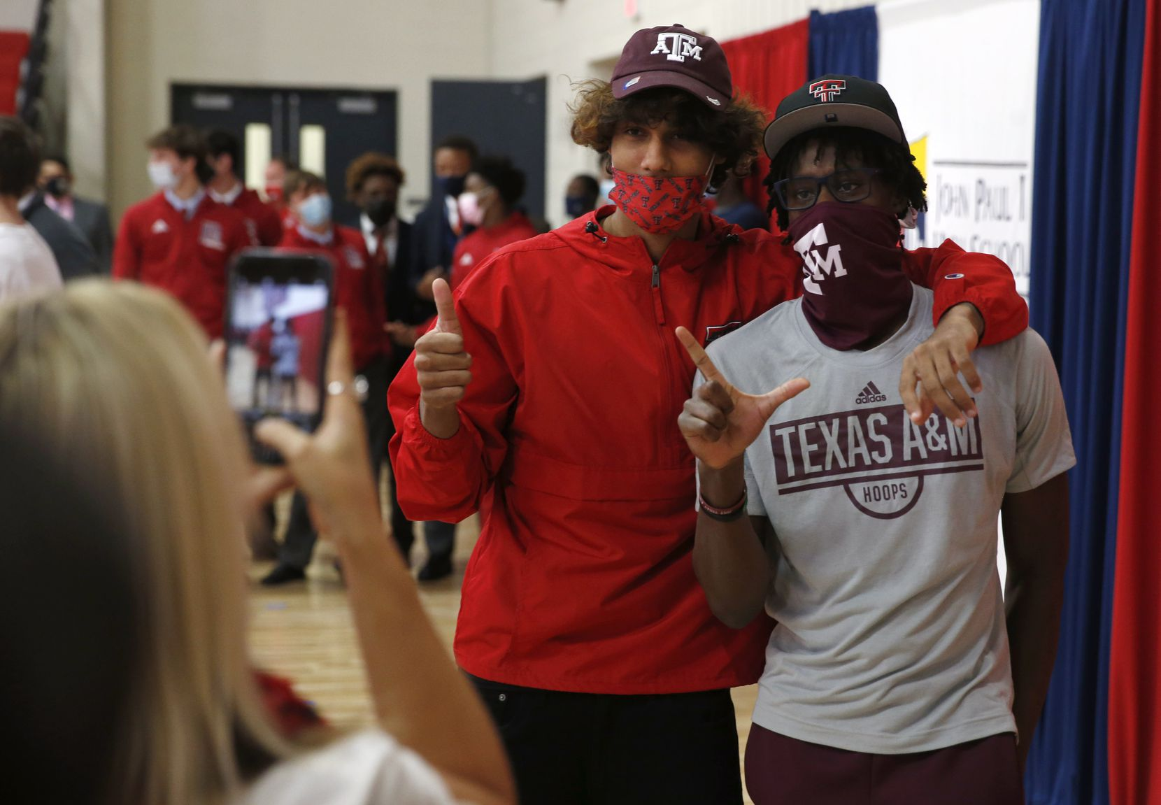 Sandra Brown takes a photo of her son, Jaylon Tyson (left) and his teammate Manny Obaseki after they signed their national letters of intent with Texas Tech University and Texas A&M University on National Signing Day at John Paul II High School on Wednesday, November 11, 2020 in Plano, Texas.