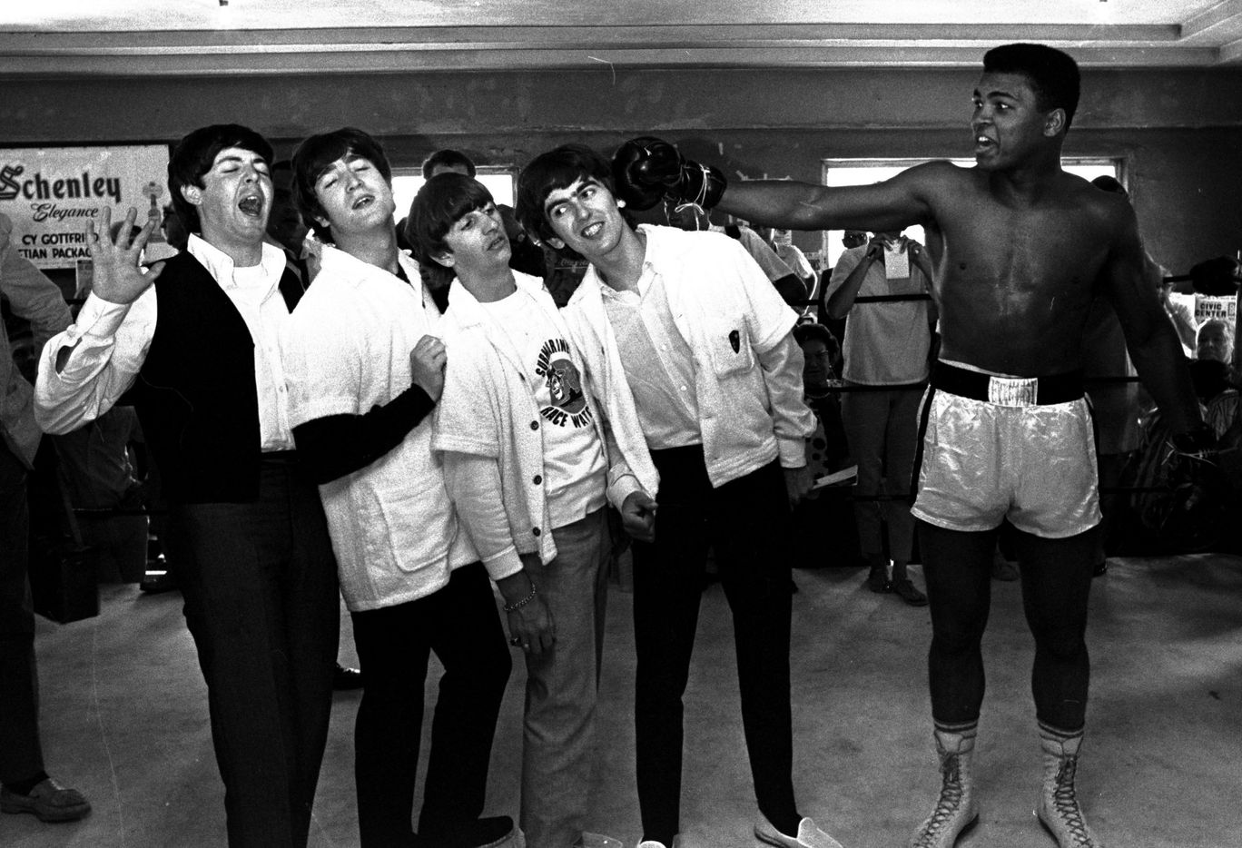 In this Feb. 18, 1964, file photo, the Beatles, from left, Paul McCartney, John Lennon, Ringo Starr, and George Harrison, take a fake blow from Cassius Clay (Muhammad Ali) while visiting the heavyweight contender at his training camp in Miami Beach, Fla.