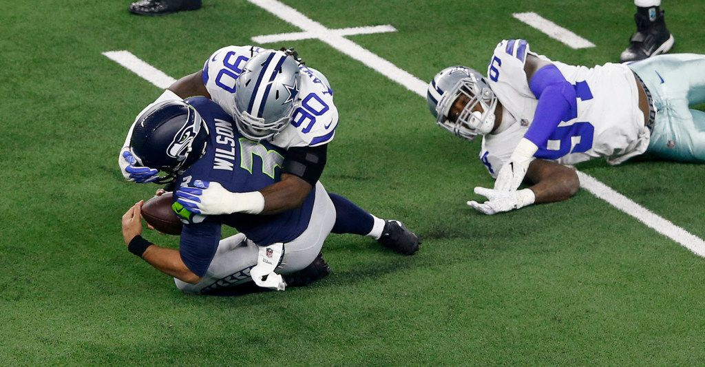 Dallas Cowboys defensive end Demarcus Lawrence (90) tackles Seattle Seahawks quarterback Russell Wilson (3) during the first half of play in a NFL playoff game at AT&T Stadium in Arlington, on Saturday, January 5, 2019. (Vernon Bryant/The Dallas Morning News)