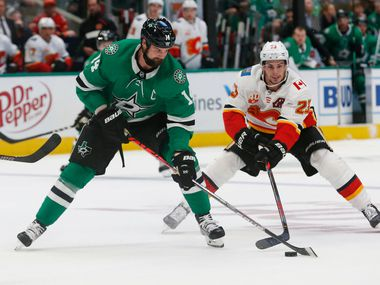 Dallas Stars left wing Jamie Benn (14) and Calgary Flames center Sean Monahan (23) vie for control of the puck during the first period of an NHL hockey game in Dallas, Thursday, Oct. 10, 2019.