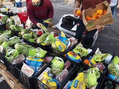Volunteers help unload and pack food supplies for families during a drive through food drive hosted by Harvest Project Food Rescue and the North Texas Dream Team, July 22, 2020 outside of East Grand Preparatory in Dallas.