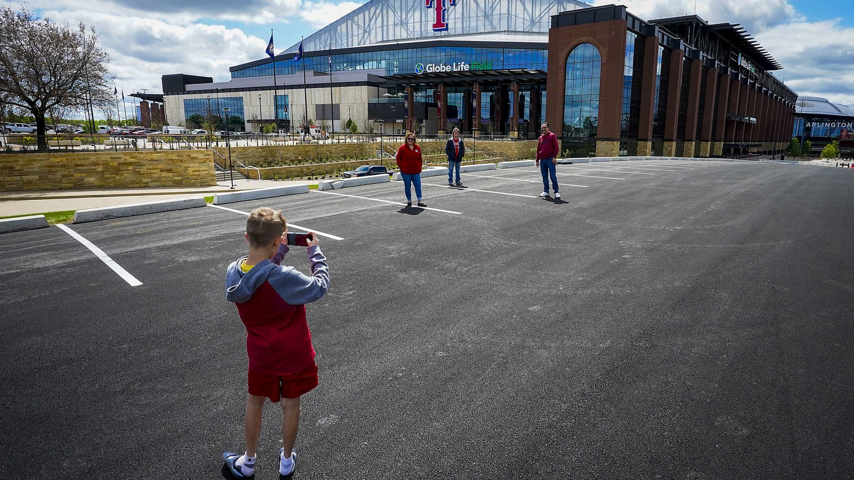 Adam Haney takes a picture of his grandmother Cheryl Springe (center) and her fellow Texas Rangers seasonal employees Eunice de la Barcena (left) and Chris Molina as they gather in the parking lot at Globe Life Field just before what would have been first pitch at the stadium on Tuesday, March 31, 2020, in Arlington, before the season was postponed due to the new coronavirus.