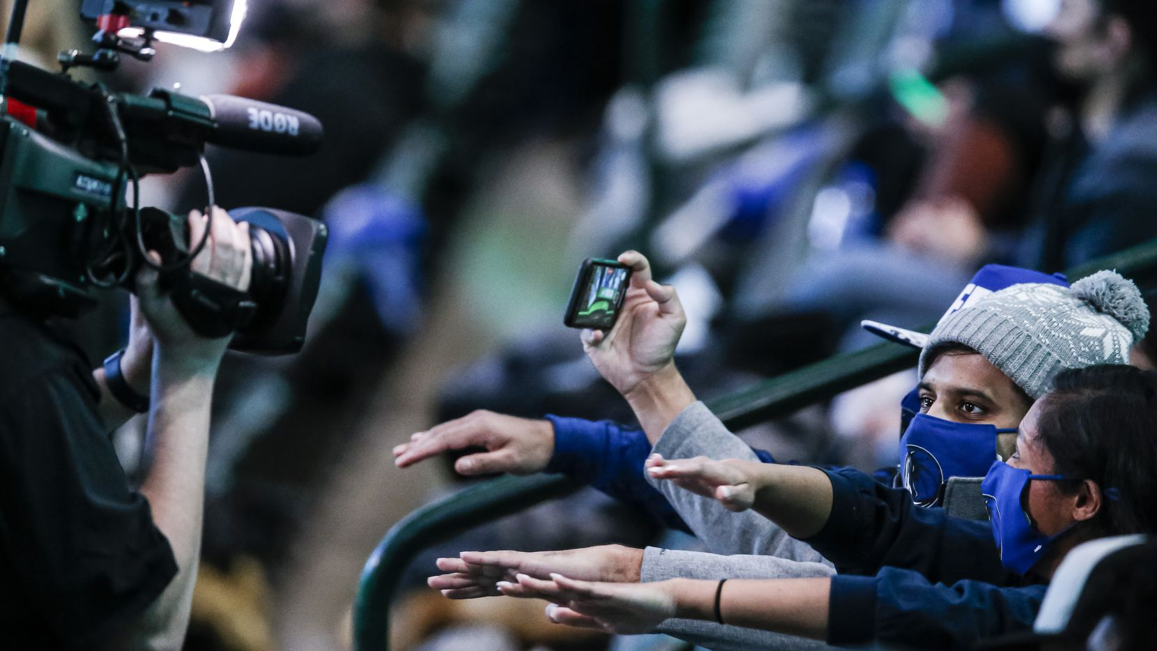 Fans, consisting mostly of healthcare workers, dance for the fan cam during a game between the Pelicans and Mavericks in Dallas on Friday, Feb. 12, 2021.