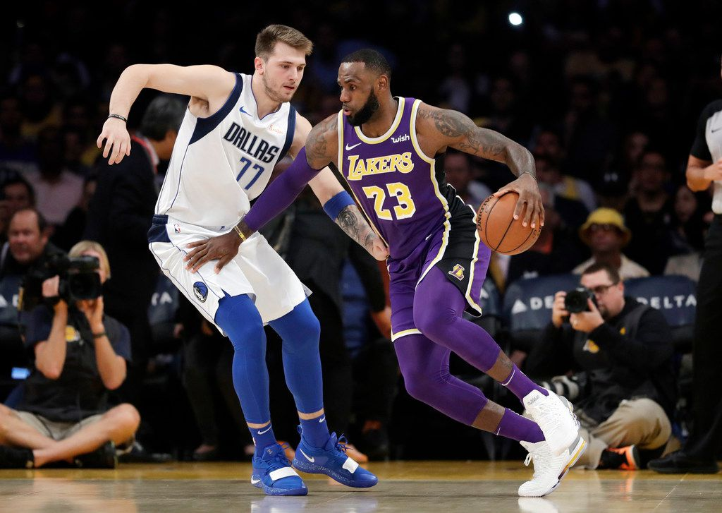FILE - Lakers forward LeBron James (23) is defended by Mavericks guard Luka Doncic (77) during the first half of a game on Wednesday, Oct. 31, 2018, in Los Angeles.