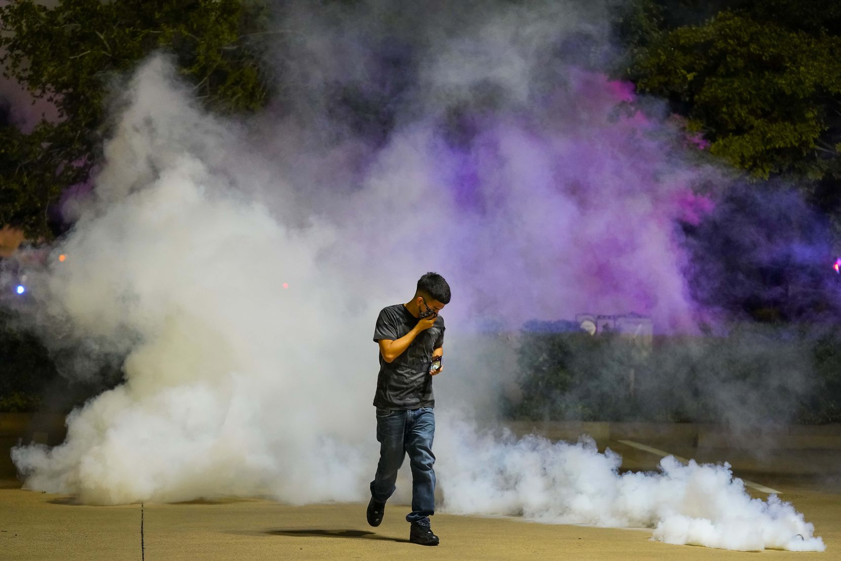 A protester runs away after a canister of teargas landed at his feat as Dallas police attempt to disperse protesters at the corner of Lamar and Young Streets as they march against police brutality on Friday, May 29, 2020, in Dallas.
