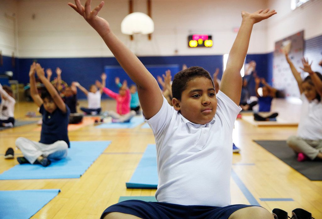 Tommie Reed, a fourth-grader in DISD's after-school program, does a yoga pose with others led by Ebony Smith, founder of Yoga N Da Hood, at B.H. Macon Elementary in Dallas on Wednesday, April 3, 2019. Yoga N Da Hood was recently awarded the Pegasus Prize, a grant of $50,000, by The Dallas Foundation for its efforts to teach self-healing and stress reduction to kids in underserved communities.