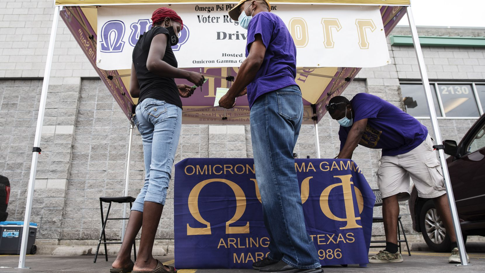 Nate Favaroth (center), a member of Omega Psi Phi Fraternity, speaks with Euniqua Marshall, 33, as she updates her voter registration information during a voter registration drive outside of the Cash Saver grocery store in South Dallas on Sept. 5, 2020. Omega Psi Phi Fraternity, part of the National Pan-Hellenic Council, conducted the registration drive.