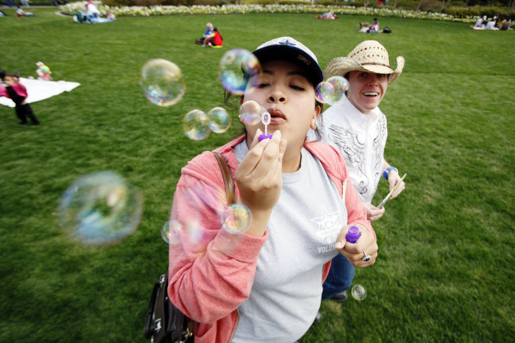 Ana Pi-a, of Fort Worth, blows bubbles while walking in the Jonsson Color Garden with Danny Stepniewski, of Arlington, during the Dallas Blooms Festival at the Dallas Arboretum.