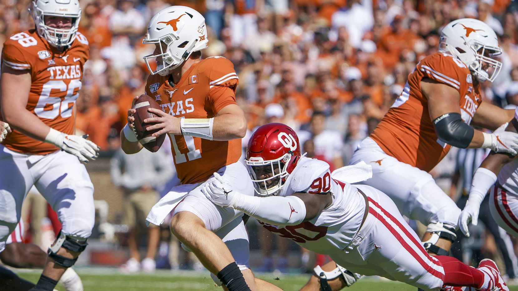 FILE - Texas quarterback Sam Ehlinger (11) is sacked by Oklahoma defensive lineman Neville Gallimore (90) during the first half of an NCAA football game at the Cotton Bowl on Saturday, Oct. 12, 2019, in Dallas.