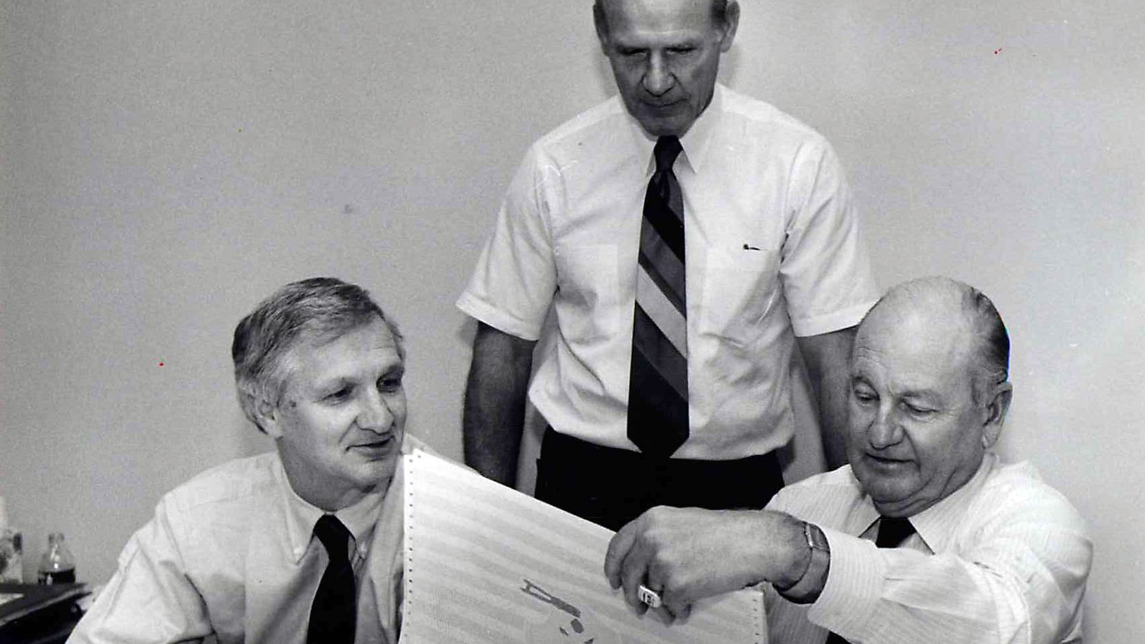 Shot April 29, 1986 - Dallas Cowboys officials Gil Brandt (from left), Tom Landry and Tex Schramm look over their choices for the second round draft picks in a conference room at Valley Ranch.