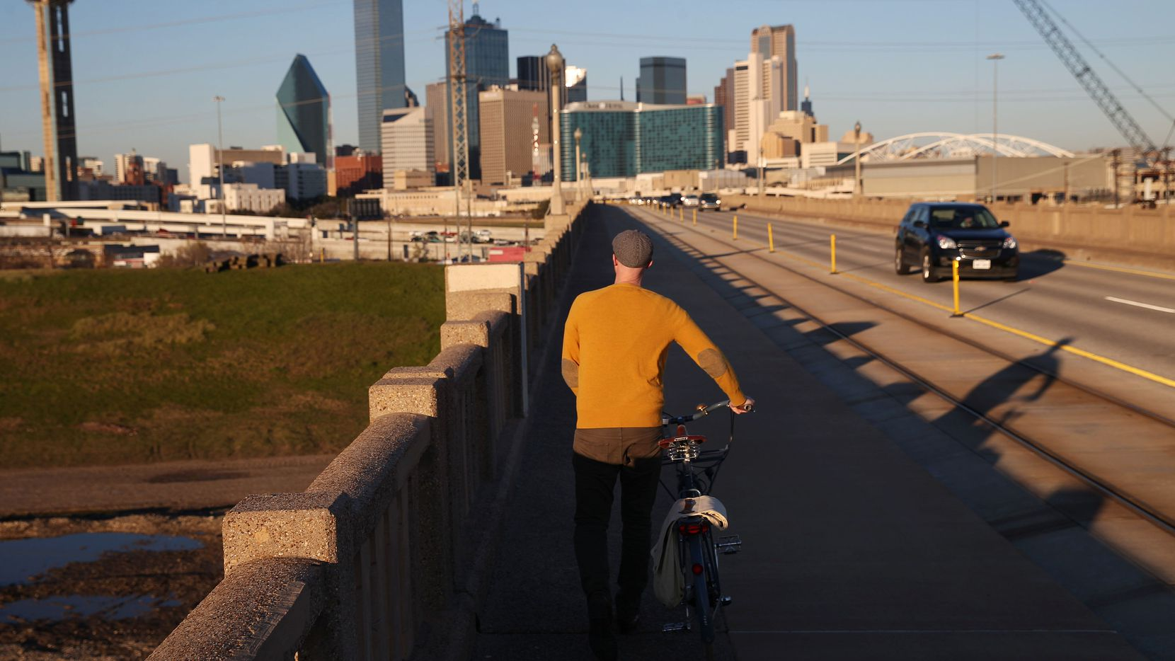 Jason Roberts, co-founder of Bike Friendly Oak Cliff, walks across the Houston Street bridge at rush hour before standing for a portrait for The Dallas Morning News in Dallas Tuesday January 12, 2016.