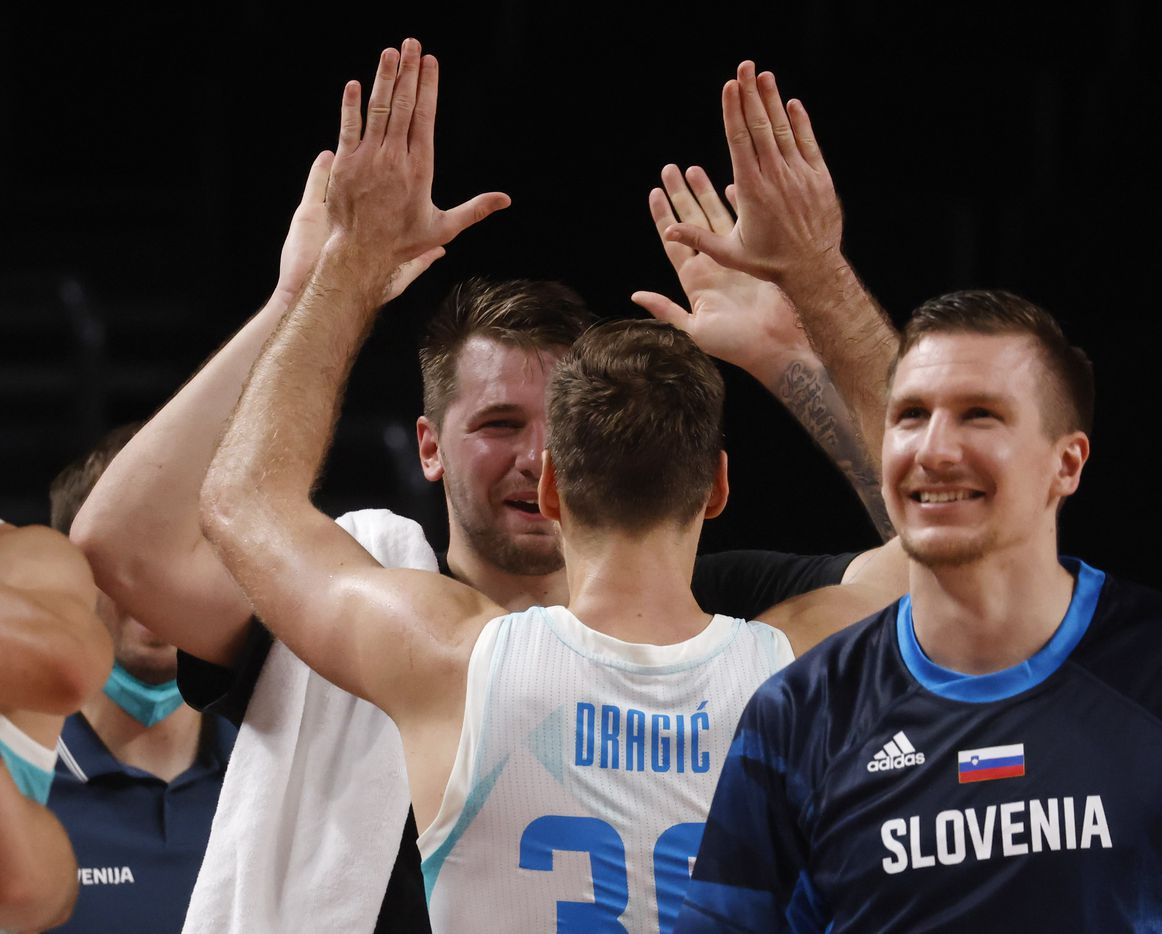 Slovenia's Luka Doncic (77) celebrates with Zoran Dragic (30) after both were pulled from play late in the game against Germany during the second half of play of a quarter final basketball game at the postponed 2020 Tokyo Olympics at Saitama Super Arena, on Tuesday, August 3, 2021, in Saitama, Japan. Slovenia defeated Germany's 94-70. (Vernon Bryant/The Dallas Morning News)
