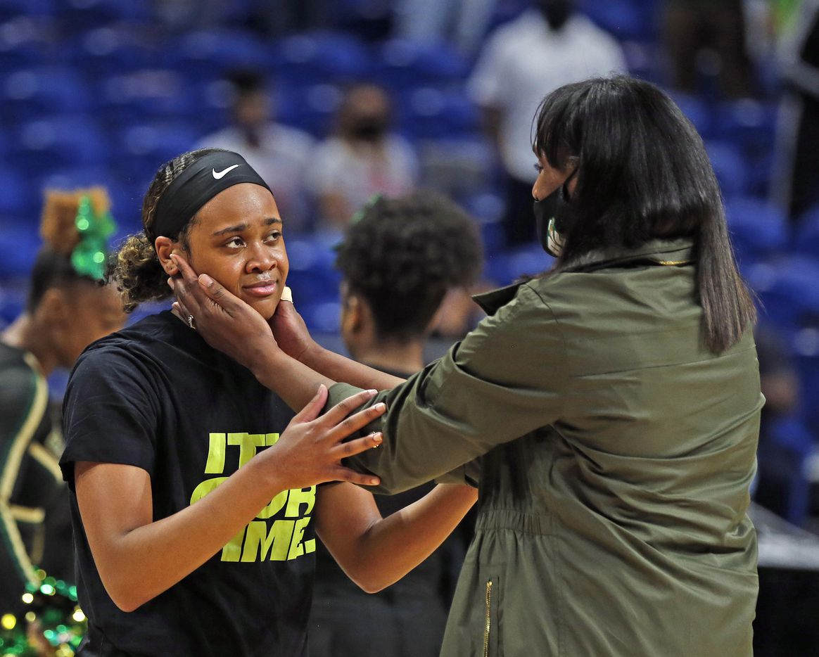An emotional DeSoto Kendall Brown #23 is congratulated by DeSoto head coach Andrea Robinson after defeating Cypress Creek.DeSoto vs. Cypress Creek girls basketball Class 6A state championship game on Thursday, March 12, 2021 at the Alamodome.