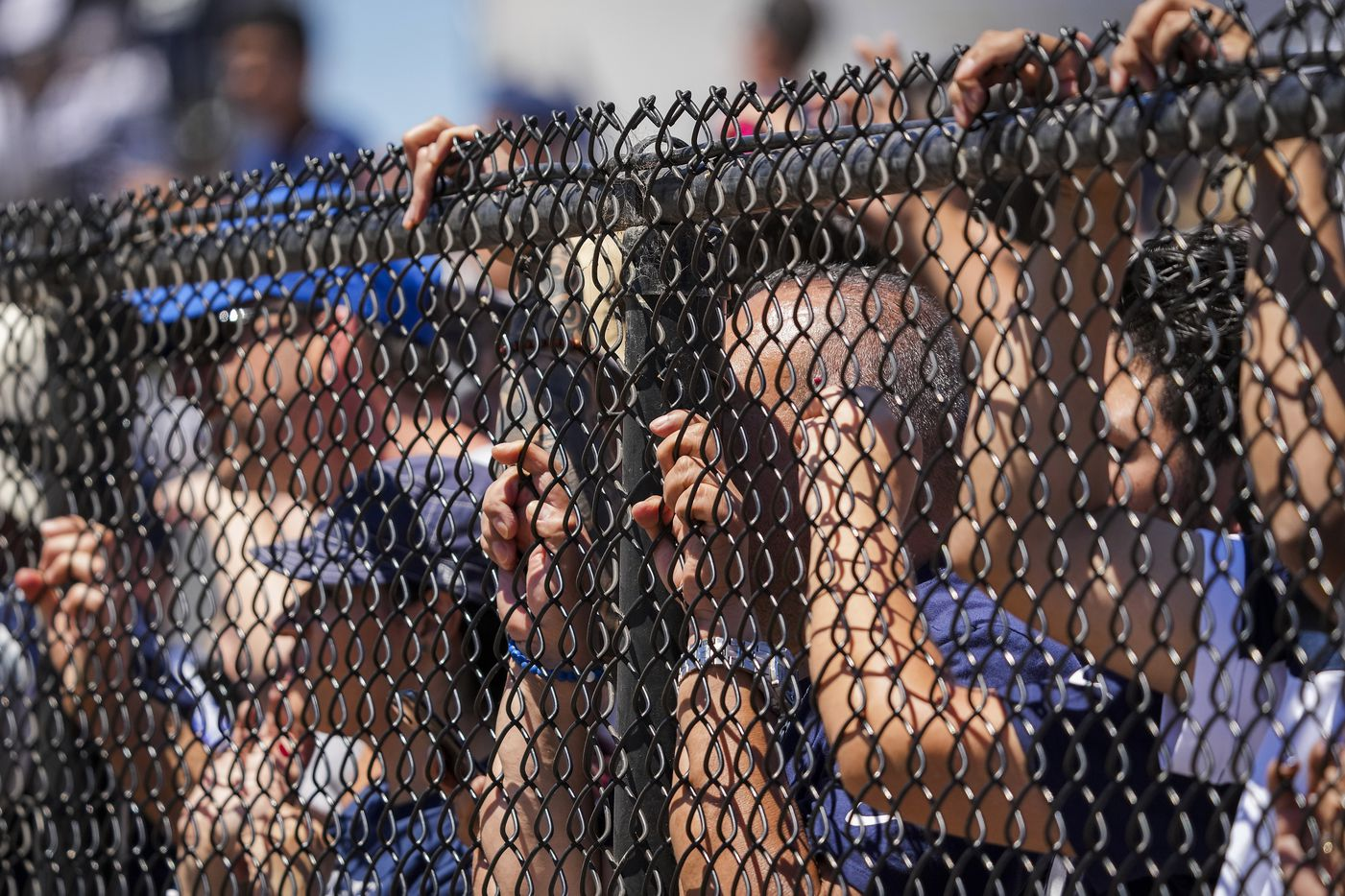 Fans press against a fence to watch the Dallas Cowboys practice at training camp on Sunday, Aug. 1, 2021, in Oxnard, Calif.