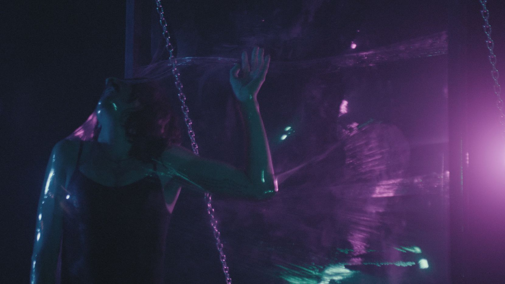 Colton James White performs a series of movements aimed at breaking through a translucent barrier of plastic wrap.