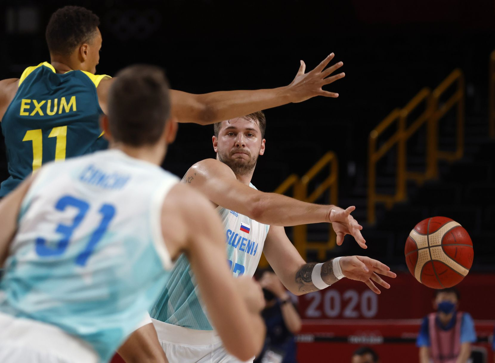 Slovenia's Luka Doncic (77) passes to Slovenia's Vlatko Cancar (31) as Australia's Dante Exum (11) defends during the first quarter of play in the bronze medal basketball game at the postponed 2020 Tokyo Olympics at Saitama Super Arena, on Saturday, August 7, 2021, in Saitama, Japan. (Vernon Bryant/The Dallas Morning News)