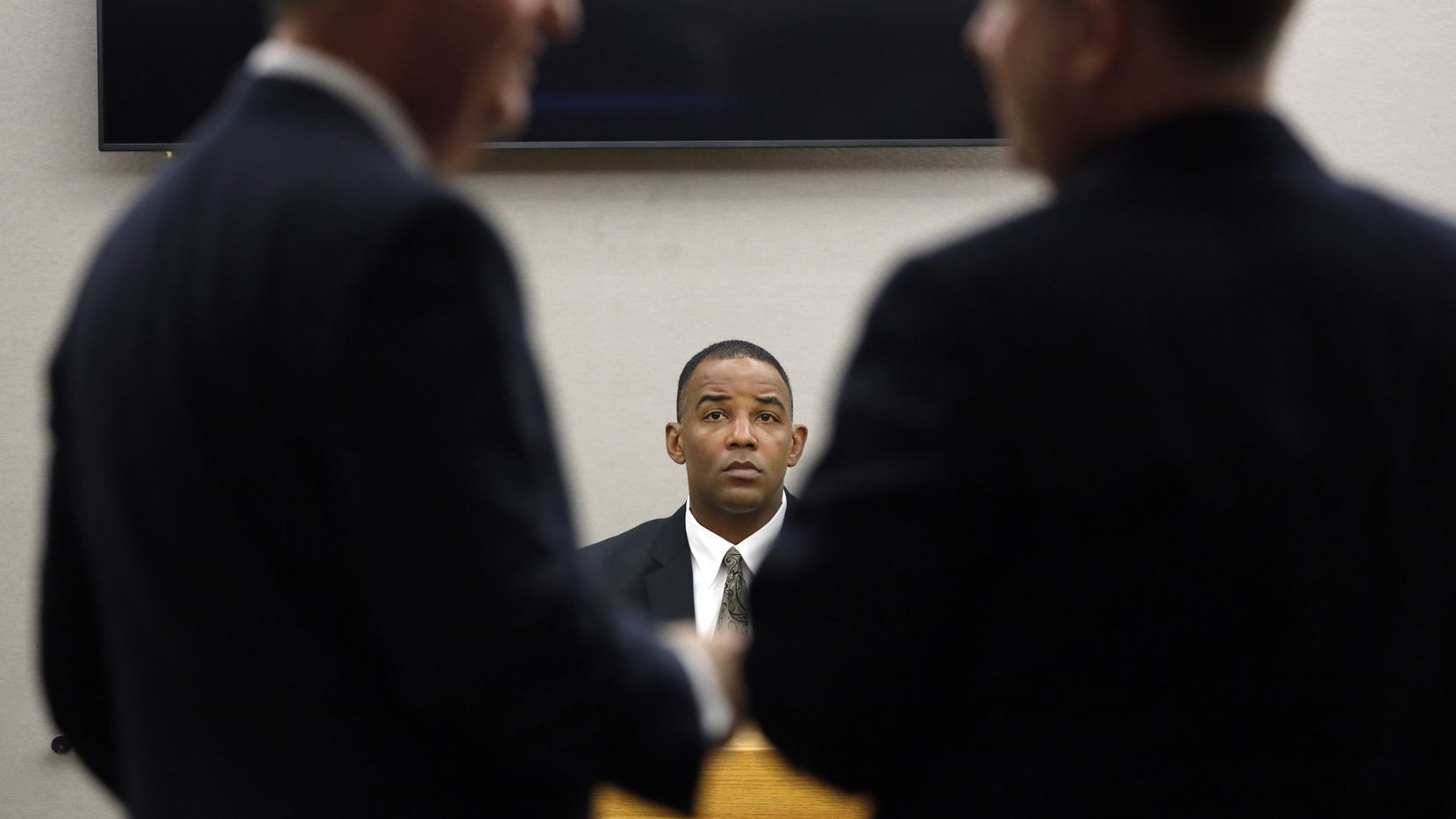 Texas Ranger David Armstrong waits for defense attorney Robert Rogers (left) and Assistant District Attorney Jason Hermus (right) discuss evidence during his questioning on the stand. Fired Dallas police Officer Amber Guygerr.
