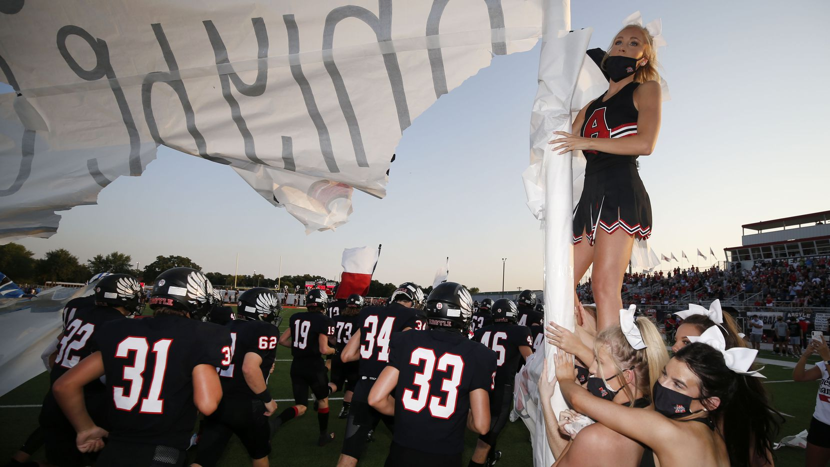 Argyle cheerleaders wear masks while holding a banner that Argyle football players ran through,during a high school football game against Decatur,  in Argyle, Tx, on August 28, 2020.