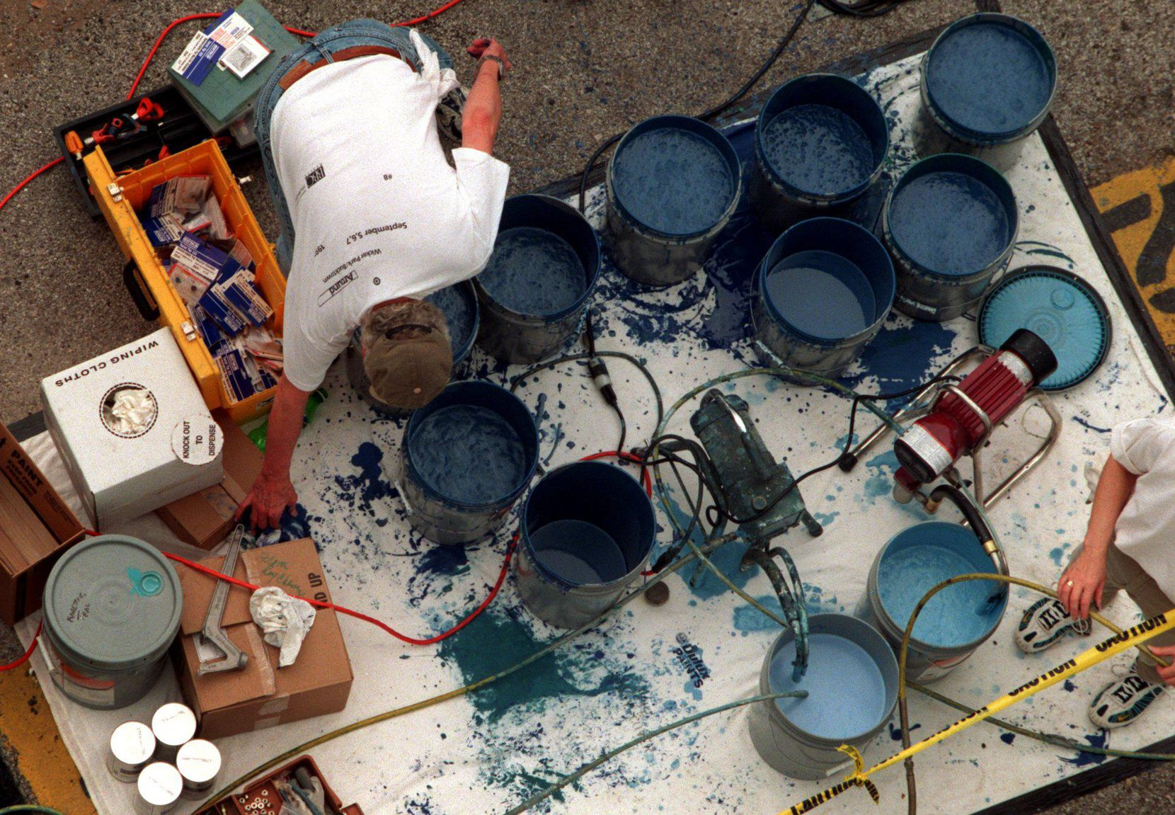 In this 1999 file photo, volunteers keep the paint pumping for Wyland the artist as he works on his whale mural that graces 505 N. Akard St.