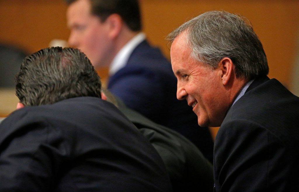 Texas Attorney General Ken Paxton (right) smiles during his pretrial hearing at Collin County Courthouse in McKinney, Texas, on Feb. 16, 2017.