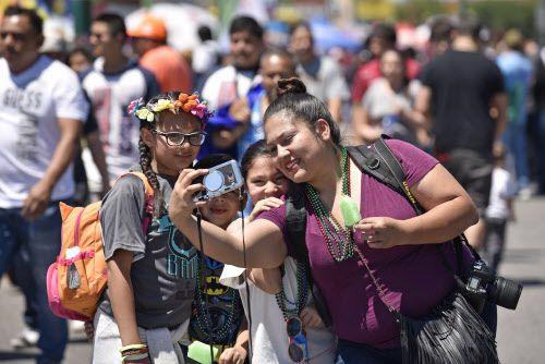 Sheila Méndez, de 30 años, se toma un selfie con su familia durante el Desfile del Cinco de Mayo en Oak Cliff.