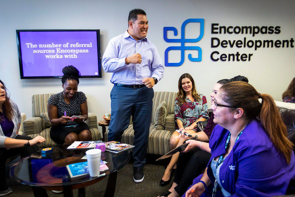 """Encompass Home Health & Hospice employee Richard Viscarra (standing) celebrates his team's correct answer while playing a game of """"Encompass Jeopardy"""" during a class at the Encompass Development Center."""