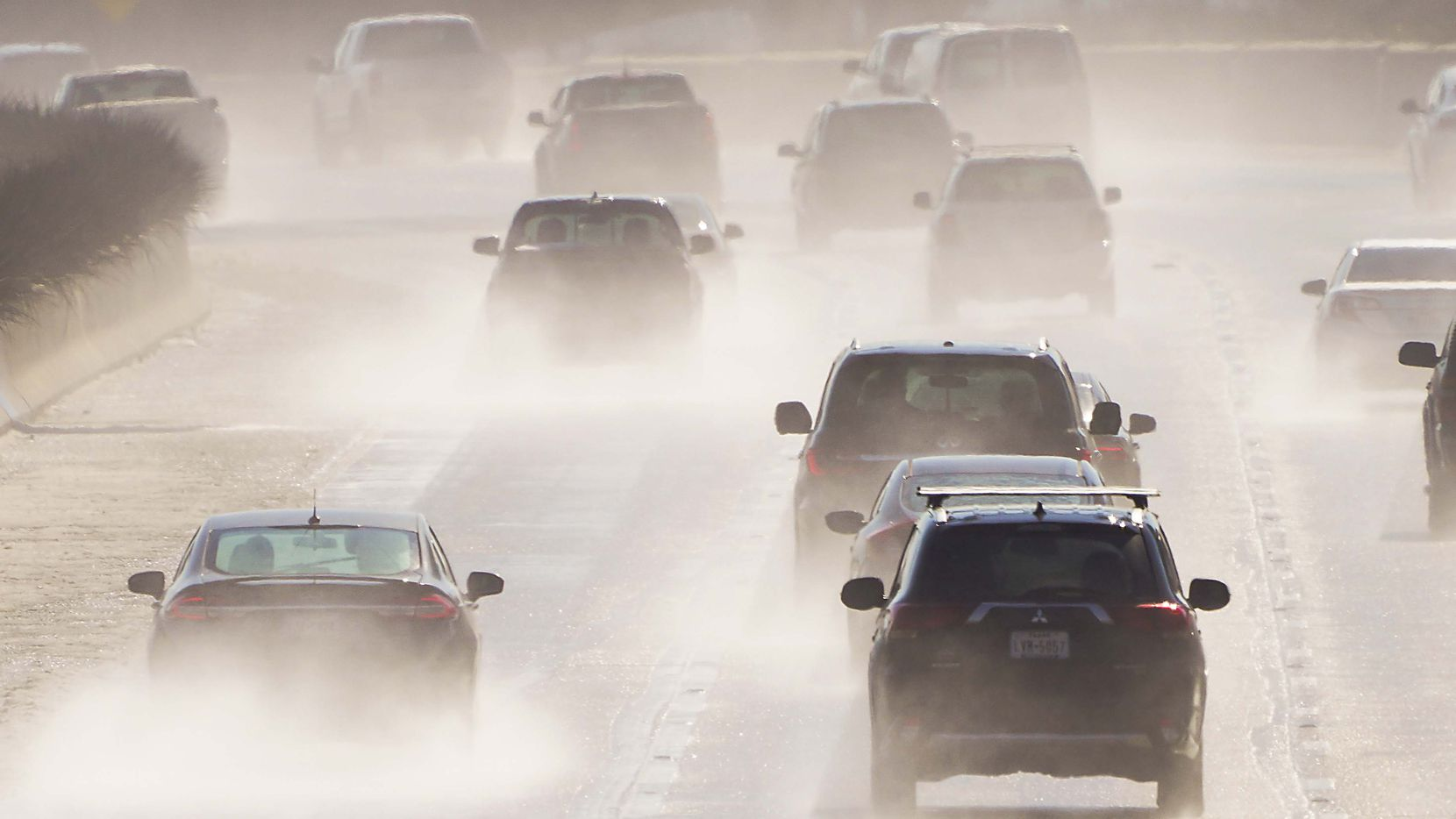 Water sprays from melting roads as traffic head south on US-75, Central Expressway, near Forest Lane as North Texas begins to thaw from  winter storms that brought snow and freezing temperatures on Friday, Feb. 19, 2021, in Dallas.