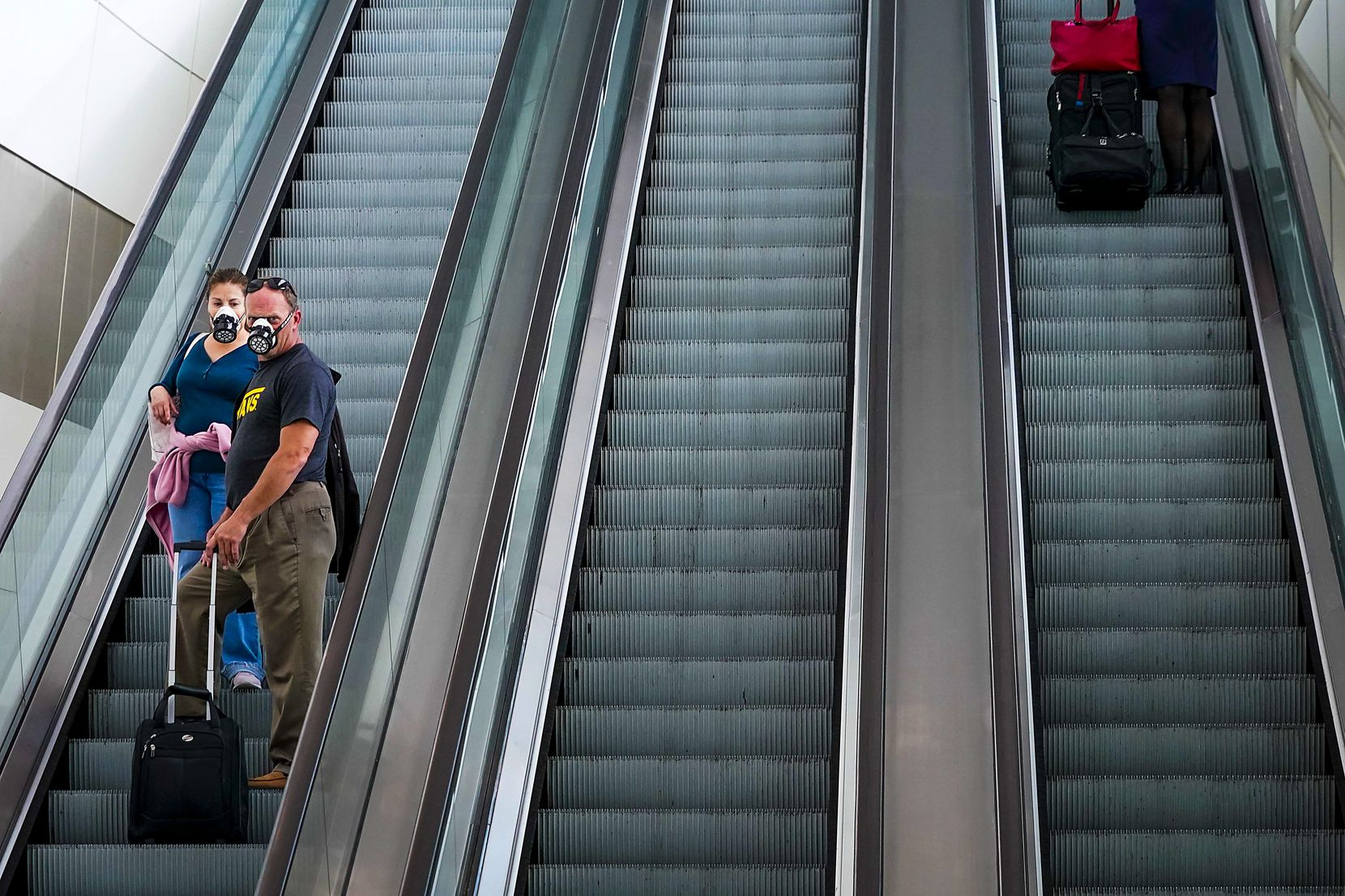 Passengers wearing face masks due to the new coronavirus rode an escalator at DFW International Airport Terminal B on March 20, 2020. For the day, TSA reported 593,167 travelers nationwide, down from 2,559,307 on the same date in 2019.